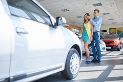 Guy prepared a surprise for his girlfriend. Buying a new car. Happy young couple looking at new car in showroom. The concept of buying a new car Royalty Free Stock Images