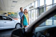 Guy prepared a surprise for his girlfriend. Buying a new car. Happy young couple looking at new car in showroom. The concept of buying a new car Royalty Free Stock Image