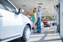Guy prepared a surprise for his girlfriend. Buying a new car. Happy young couple looking at new car in showroom. The concept of buying a new car Stock Photos