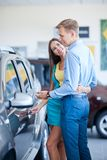 Guy prepared a surprise for his girlfriend. Buying a new car. Happy young couple looking at new car in showroom. The concept of buying a new car Royalty Free Stock Photography