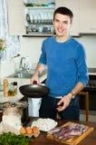 Guy preparing skillet for calamary. Smiling guy preparing skillet for cooking calamary rings Royalty Free Stock Image