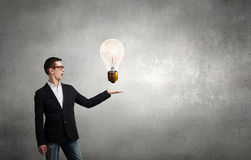Guy presenting bright idea . Mixed media Royalty Free Stock Images