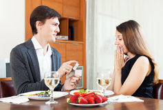 Guy presenting to amazed woman engagement ring in box at table. Young guy presenting to amazed women engagement ring in box at table Royalty Free Stock Images