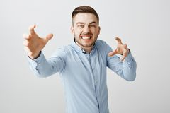 Guy pretending he vampire wanting eat blood. Funny emotive stylish european male with bristle with stylish haircut stock photo
