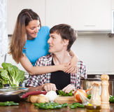 Guy and pretty girl cooking in domestic kitchen Stock Images
