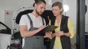 Guy pro advises client, woman and master near machine, visitor in auto stock footage