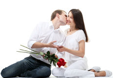 Guy proposing ring to his girlfriend. Couple in love: guy kissing his smiling girlfriend and proposing ring and red roses to her; isolated on white background Stock Image