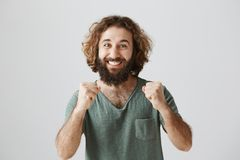 Guy is proud of brother. Portrait of grinning excited easter man with beard and curly hair clenching fists near chest. And smiling broadly from success or Royalty Free Stock Images