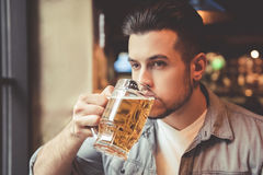 Guy at the pub. Handsome guy is drinking beer while resting in pub Stock Photography