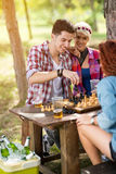 Guy pulls a move in chess game on picnic Stock Photography
