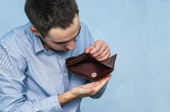 The guy pulls out the last ruble out of an empty purse. Poverty and unemployment. Man with no money. Businessman holding empty wallet royalty free stock photos
