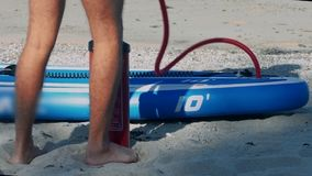 Guy pumps fast paddle board through pipe low-angle shot. Low angle close shot strong guy pumps blue and white paddle board with red hand pump through pipe on stock video