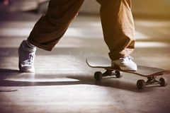 A guy pushes off the floor and rides a skateboard stock image