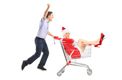 Guy pushing a cart and female in christmas costume Royalty Free Stock Image