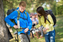Guy put map in pocket and girl gives him fresh water Stock Images