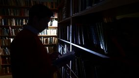 The guy puts the book in its place in the library stock footage