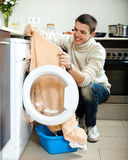 Guy  putting clothes in to washing machine Royalty Free Stock Photography