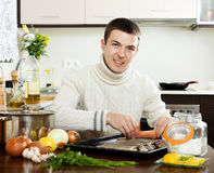 Guy putting   fish into sheet pan Royalty Free Stock Images