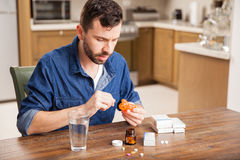 Guy putting pills on a box at home Royalty Free Stock Photo