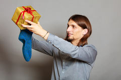 Guy putting wrapped gift in knitted christmas sock Stock Photo