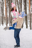 The guy raised his beloved girlfriend to the hands and spins, winter outdoors Royalty Free Stock Image