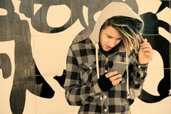 Guy  with rasta hair watching his smart-phone warm filter applie Stock Images