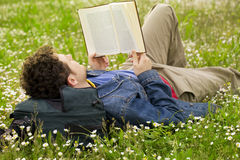 Guy reading 03. Guy laying on the grass and reading a book Stock Photography