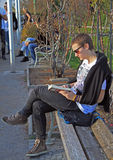 Guy is reading a book at the bench in Graz Royalty Free Stock Photography