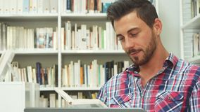 Smart guy is reading a book. The guy is reading a book. He looks very attentive and relaxed. He sits on the floor in the library stock video footage