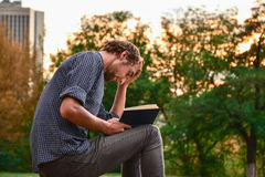 Guy reading book in park Royalty Free Stock Photography