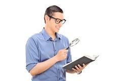 Guy reading a book through a scrutiny Stock Photography