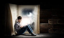 Guy reading book. Teenager boy wearing jeans and shirt and reading book Stock Photography