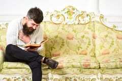 Guy reading old book with enjoyment. Humorous literature concept. Macho on laughing face reading book. Man with beard. And mustache sits on baroque style sofa royalty free stock images