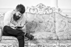 Guy reading old book with enjoyment. Humorous literature concept. Macho on laughing face reading book. Man with beard. And mustache sits on baroque style sofa royalty free stock photo