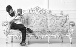 Guy reading old book with enjoyment. Humorous literature concept. Man with beard and mustache sits on baroque style sofa. Holds book, white wall background royalty free stock image