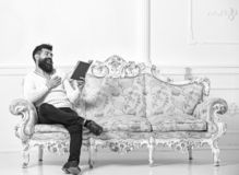 Guy reading old book with enjoyment. Man with beard and mustache sits on baroque style sofa, holds book, white wall. Background. Macho on laughing face reading stock photos