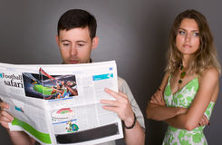 Guy reading soccer newspaper, girl upset Royalty Free Stock Photos