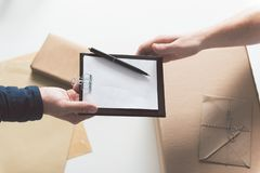 Guy is receiving mail at work. Express delivery. Close-up top view of hands of courier and recipient male. They are holding folder with invoice. Envelope and box Royalty Free Stock Images