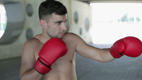 The guy in a red boxing gloves standing outdoors. stock footage