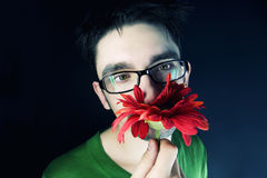 Guy with a red flower on a black background Royalty Free Stock Photos