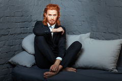 Guy with  red hair and beard, sitting on the sofa. Royalty Free Stock Photos