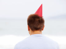 Guy in red hat near sea from behind Stock Photo