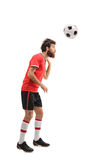 Guy in a red jersey heading a football Royalty Free Stock Images