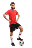 Guy in red jersey pressing a football with his foot Stock Images