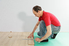 Guy in red measuring plank Royalty Free Stock Photos