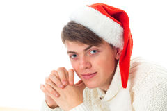 Guy in red santa hat looking at the camera. Cheerful guy in red santa hat looking at the camera and smiling isolated on white background Royalty Free Stock Photo