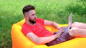 The guy in the red T-shirt lying on an inflatable mattress working on a laptop. A young man with a beard is a freelancer in nature