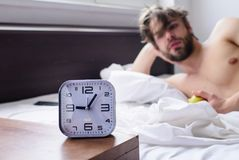 Guy relaxing bed before alarm clock ringing. Important part of morning. Get up early morning tips. Man bearded unshaven. Handsome guy lean on hand while eats stock photography