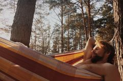 Guy relaxing in the hammock in a wood Royalty Free Stock Photo