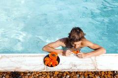 Free Guy Relaxing In Pool And Eating Papaya Stock Photos - 140268293